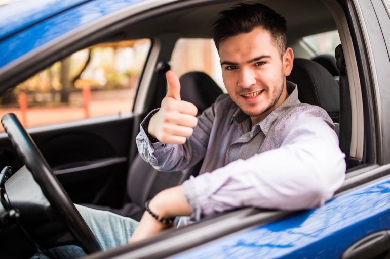 Happy man sitting in a van showing thumbs up